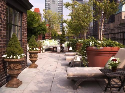 Städtischer Balkon Steinboden Topfpflanzen Kissen Liegen groß verziert