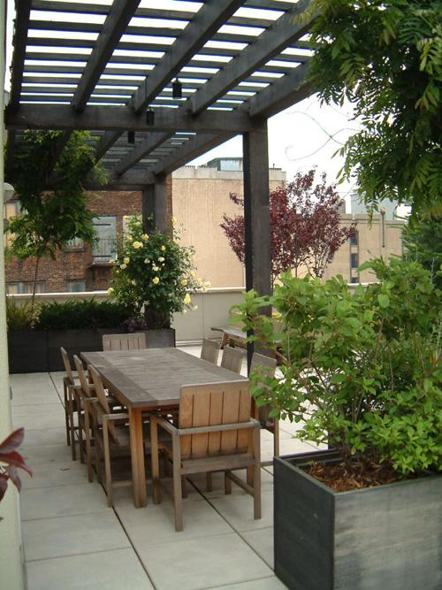 Urbanische Dachterrasse Holztisch Stühle Blumentopf Steinboden