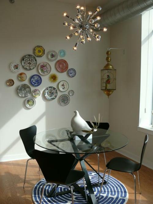 esszimmer rund glastisch schwarz akrylmöbel- wandteller collage extaravagant kronleuchter