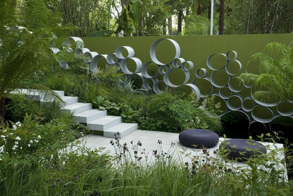 gartenideen betonfliesen sitzkissen metallene dekoration treppe sommerpflanzen terrasse