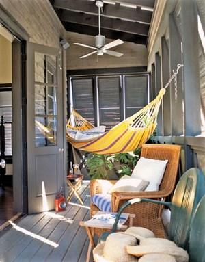 gelbe hängematte rattanstuhl kleiner tisch veranda