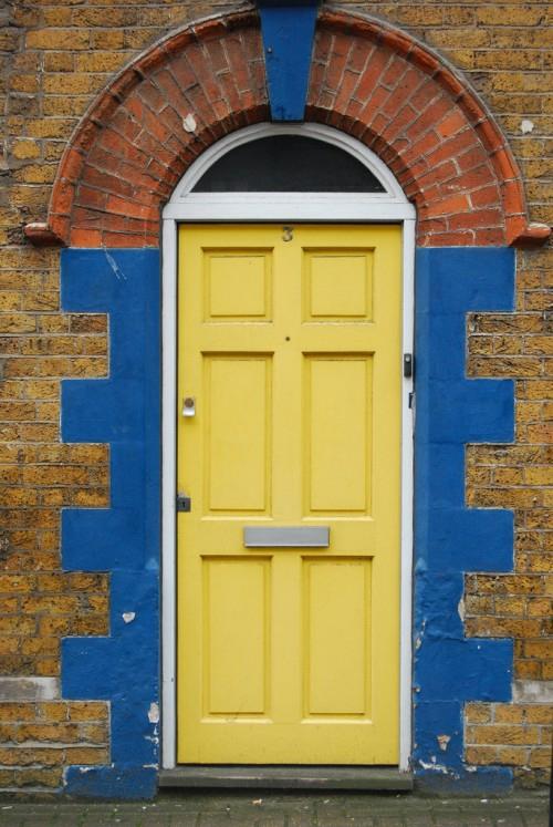 gelbes haustür design originell blau ziegelmauer