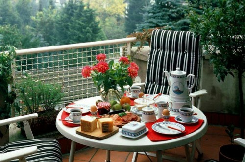 gitter balkon gemütlich rund tisch streifen schwarz weiß blumen rot frühstückstisch