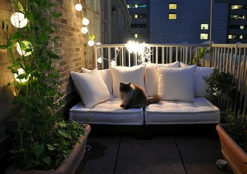 ideen gemütlichen balkon katze romantik leuchten lichterkette weiße möbel