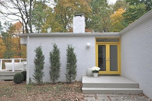 weiß exterieur ziegelmauer gelb haustür pflanzen