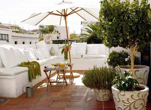weißes großes Sofa Steinfliesen Dach Balkon Sonnenschirm
