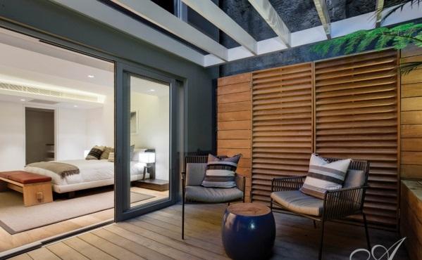 Balkon mit Holzboden, Sofa, Rattan Kaffeetisch und Pflanzkübeln