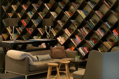 haus bibliothek rautenförmig wand regale sofa sessel hocker holz
