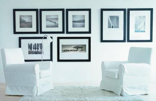 wand dekoration mit bildern schwarze rahmen weiße einrichtung sessel