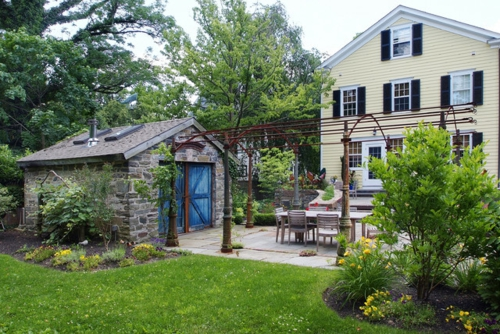 Gartenhaus im Hinterhof baum steinwand fassade holz tor