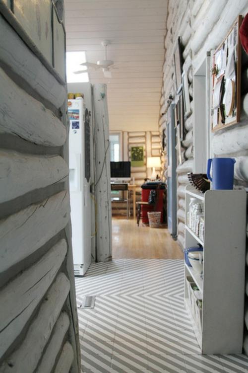 blockhaus aus holz gestreifter boden im flur weiß und hellgrau