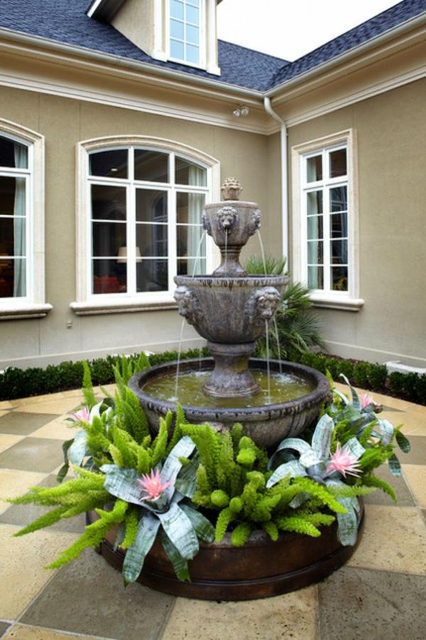 exotische dekoration mit tropische pflanzen dreistufiger wasserbrunnen rosa blüten