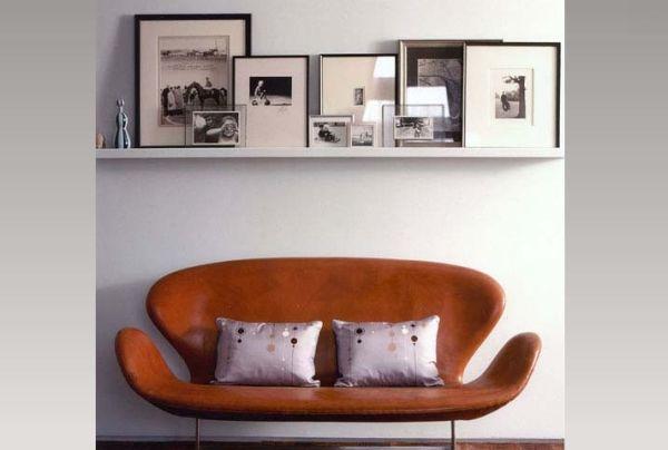 schwarz weiß bilder gestapelt über designer sofa in dunkel orange