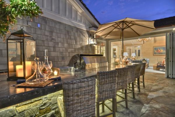 veranda party im sommer geräumige bartheke rattan stühle stein bodenbelag