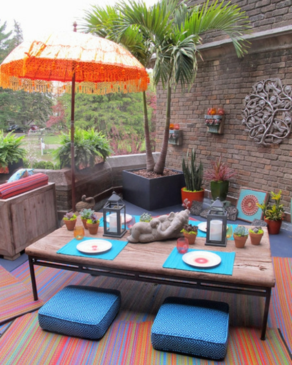 veranda party im sommer mit indischem flair statuetten und sonnenschirm in orange