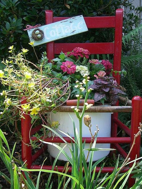 Alte Stühle im Garten mit neuer Funktion rot attraktive Pflanzgefäße