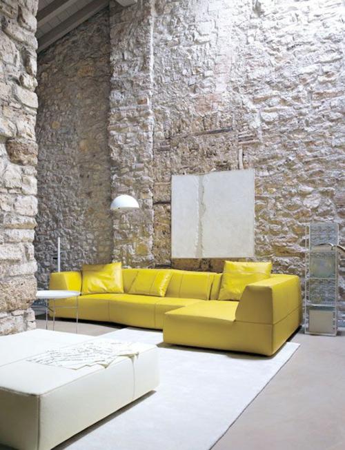 gelb leder sofa kissen raue steinwände weiß tisch teppich