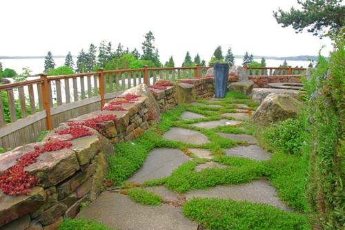 steinplatten im garten saftiges gras rote pflanzen