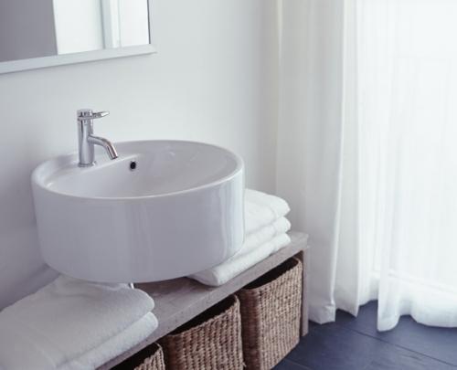 weiße Farbe im Badezimmer waschbecken rund strohkorb tücher