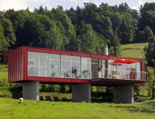 freistehend haus rot fassade metall container glas veranda balkon