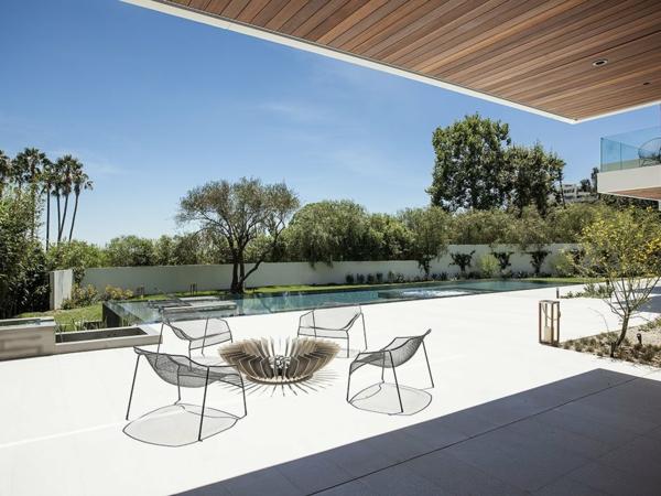 luxuriöse residenz mit gewagtem design korbsessel und offene feuerstelle