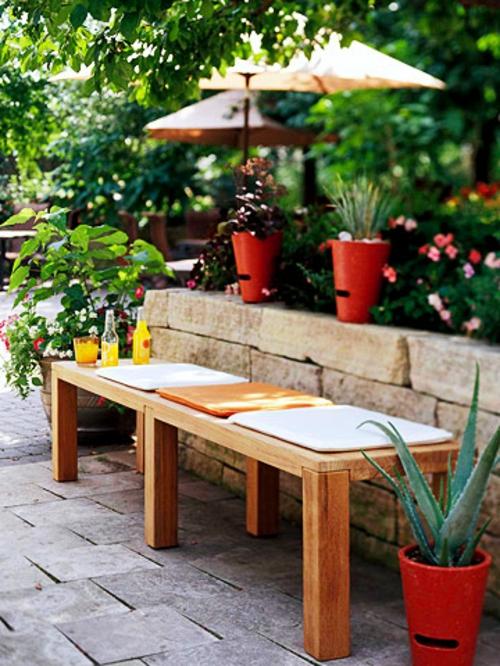 schattige Sitzecke im Garten getränke holz sitzbank auflagen farben