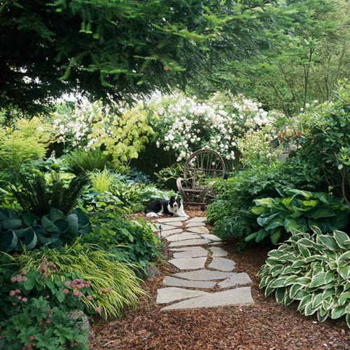 schattige Sitzecke im Garten holz stühle blumen pflanzen pflaster fußweg