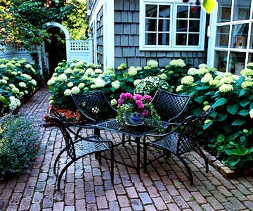schattige Sitzecke im Garten metallisch stühle blumen strukturen