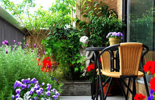 terrassengestaltung mit pflanzen rattan stühle und gips statue