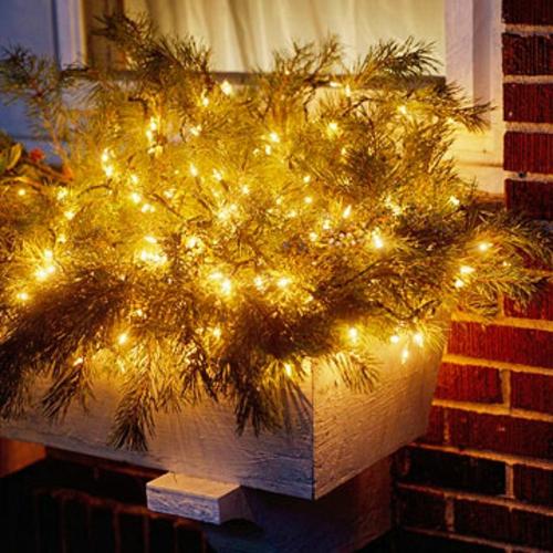 Festliche Gartenbeleuchtung zu Weihnachten zweige ziegel fassade