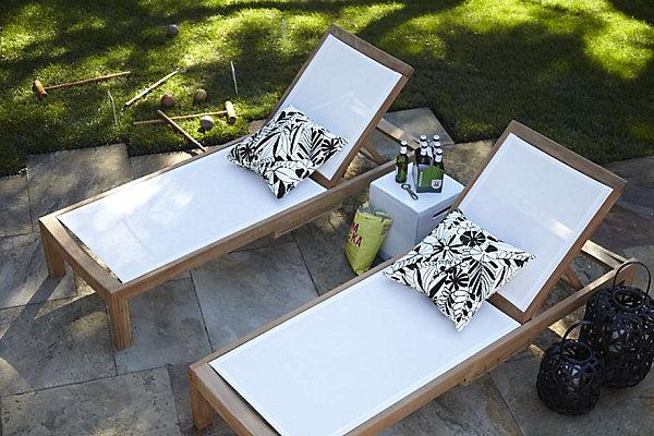 stilvolle gartenstühle liegen aus teakholz und weißem leinen
