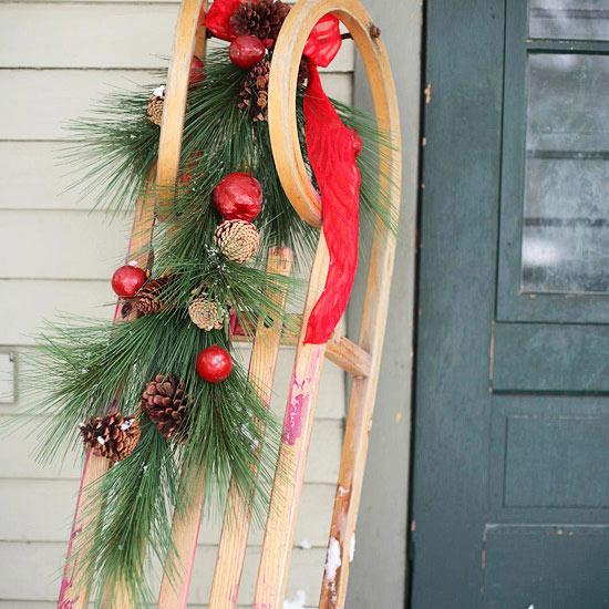 weihnachten außendekoration schlitten mit deko obst zapfen und ästen