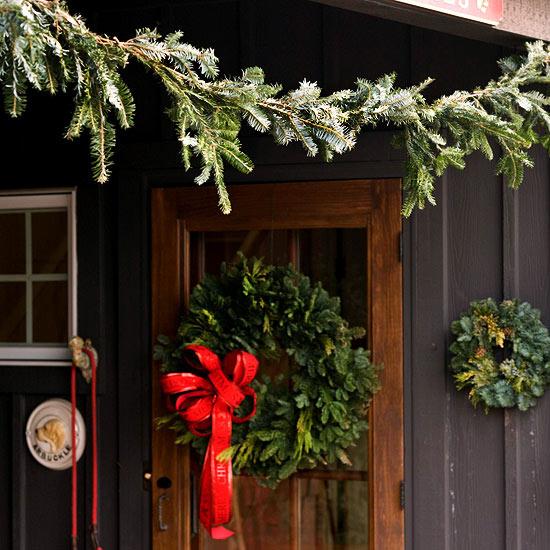 weihnachtsdekoration draußen kranz immergrün tür rot schleife