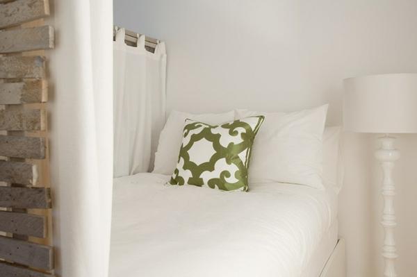 einzimmerwohnung schneeweiße bettwäsche und olivengrüne muster kissen
