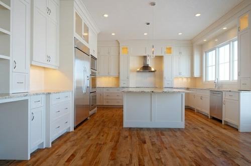 holzboden in der küche weiße Schränke und Kücheninsel