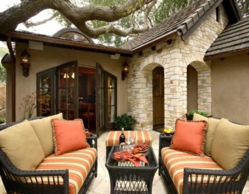 veranda mit Naturstein gestalten orange dekokissen
