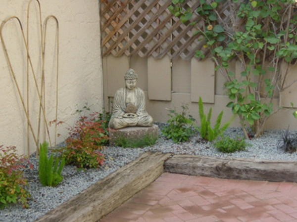 Buddha Figuren im Garten grün kanten beete kies