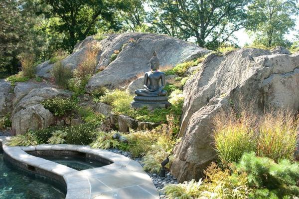 Buddha Figuren im Garten grün laub steine felsen