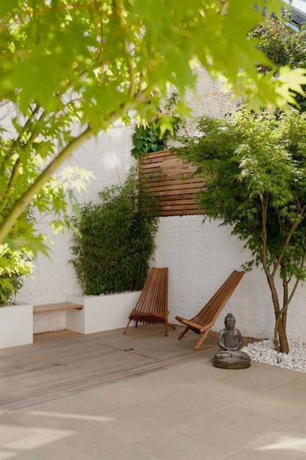 Buddha Figuren im Garten grüne umgebung holzplatten hängematte