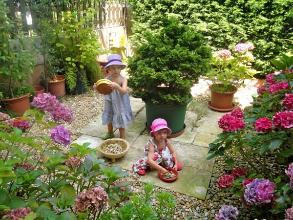 kleinen garten anlegen innenhof steinplatten kacheln kieselsteine hortensien