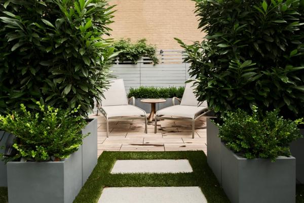 sichtschutz für terrasse üppige bepflanzung holzdielen liegen
