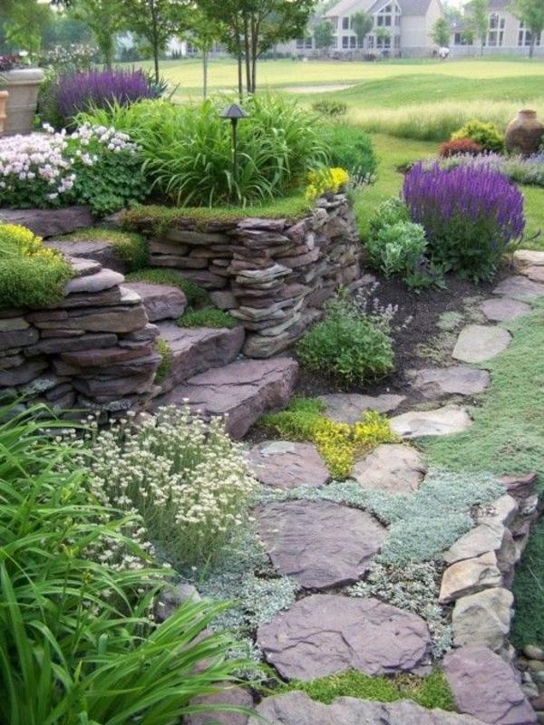 steingarten mit steinmauer gestapelte steine bunte pflanzen