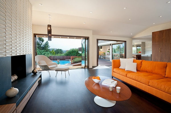 wohnzimmer einrichten glastüren pool moderner kamin sofa in orange