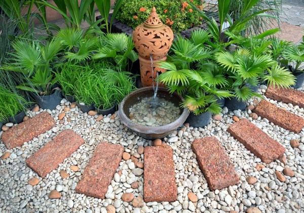 zierbrunnen steinblöcke kieselsteine palmen gartenideen fernöstlich