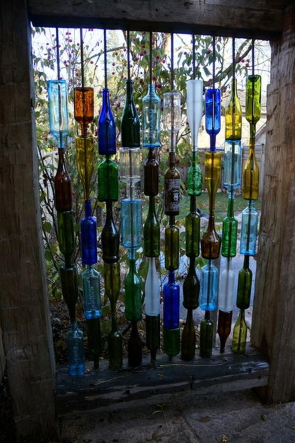 decoração eclética de garrafas coloridas de jardim