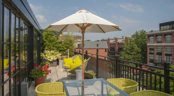 dachterrasse gestalten balkon dekorieren sonnenschirm rattan sessel in gelb