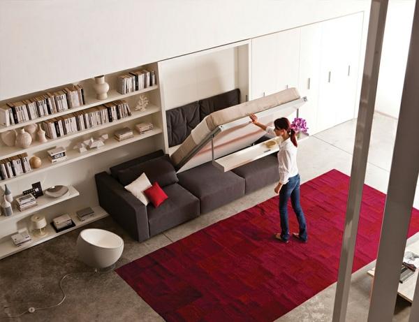 klappbett sofa roter teppich offenes regalsystem