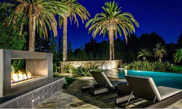 außenbereich gestalten kamin gartenpool relax liegestühle palmen gartenbeleuchtung