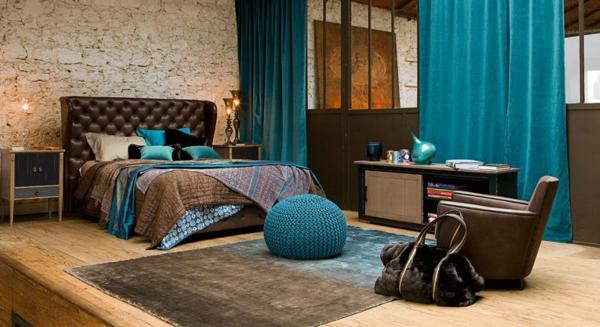 schlafzimmer gestalten bettpolsterun leder braun steinwand holzdielen gestrickter pouf blau vorhänge samt salvationrus