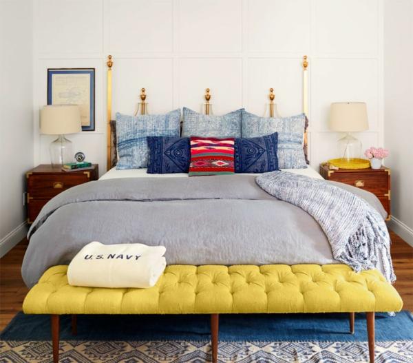 schlafzimmer gestalten metallbett kopfteil bunte dekokissen bettbank gelb retro nachtkonsolen tischleuchten